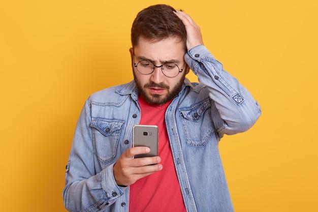 Foto van de charismatische geschokte jonge gebaarde mens die zijn smartphone houdt, aandachtig bekijkend het scherm van het apparaat, hand op het hoofd zet