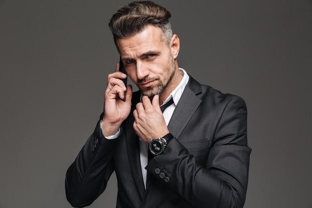 Foto van de gebaarde rijpe mens die in bedrijfskostuum op camera kijken terwijl het hebben van mobiel gesprek, dat over donkergrijs wordt geïsoleerd