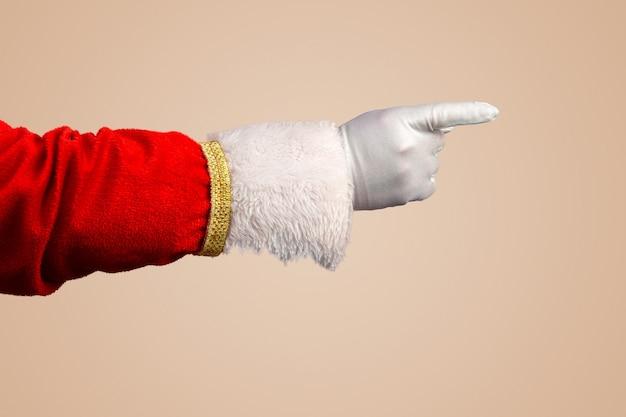 Foto van de gehandschoende hand van de kerstman in een wijzend gebaar de kerstman wijst met zijn vingers over pastel