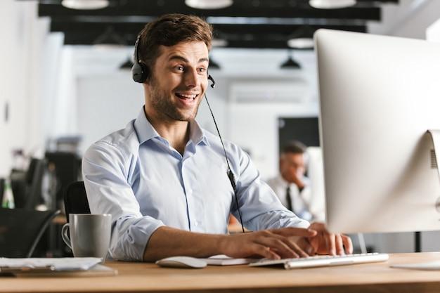 Foto van de gelukkige 20s die van de exploitantman bureaukleren en hoofdtelefoon dragen, die door computer in call centre zitten