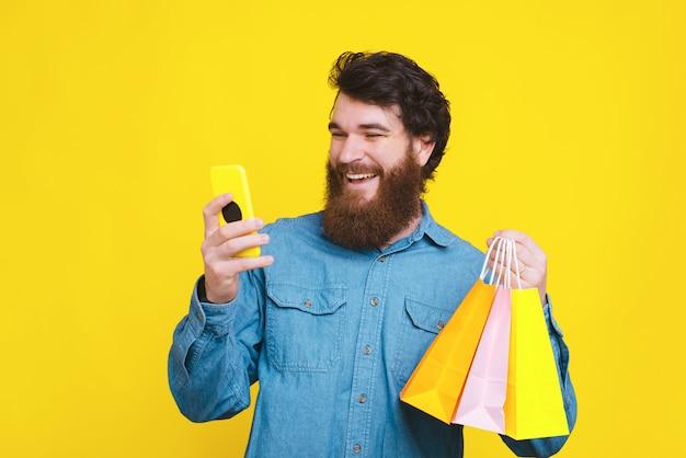 Foto van de gelukkige gebaarde hipstermens gebruikend smartphone en het houden van het winkelen zakken
