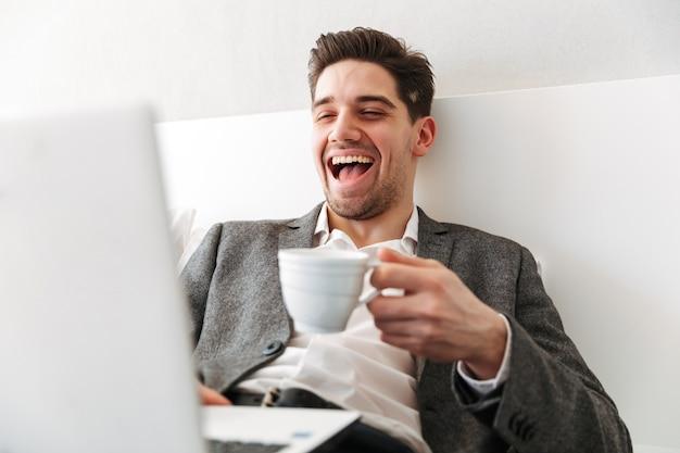 Foto van de gelukkige mens in zakelijke kleren die in lachen uitbarsten, terwijl het rusten in bed met laptop en het drinken van koffie