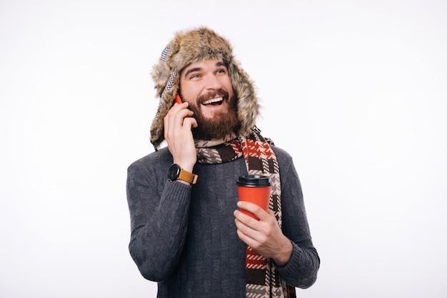 Foto van de gelukkige mens met baard in de winterkleren die op telefoon spreken en kop van koffie houden om te gaan