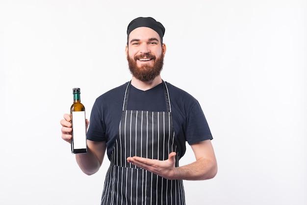Foto van de gelukkige mens van de chef-kok met baard die nieuwe olijfoliefles copyspace tonen