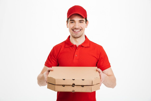 Foto van de gelukkige mens van de leveringsdienst in rode t-shirt en glb die voedselorde geven en twee pizzadozen houden, die over witte ruimte wordt geïsoleerd