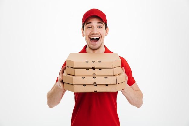 Foto van de gelukkige mens van de leveringsdienst in rode t-shirt en glb-holdingsstapel pizzadozen, die over witte ruimte wordt geïsoleerd