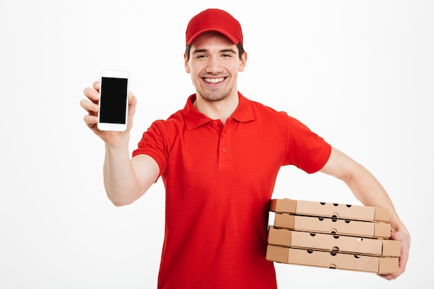 Foto van de gelukkige mens van de leveringsdienst in rode t-shirt en glb-holdingsstapel pizzadozen en het tonen van smartphone, die over witte ruimte wordt geïsoleerd