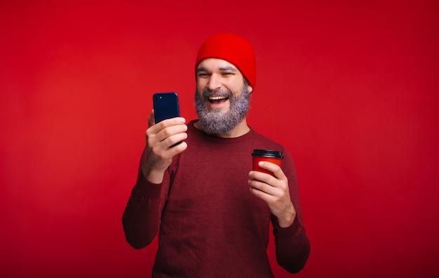 Foto van de glimlachende gebaarde mens in rood die telefoon bekijken en kop van koffie houden