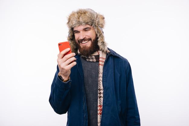 Foto van de glimlachende mens die in de winterkleren zijn smartphone bekijkt