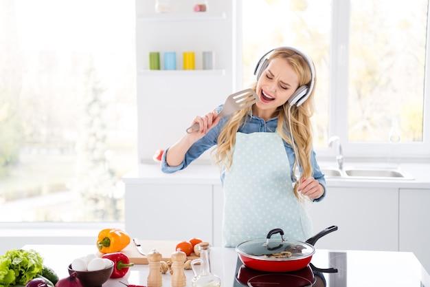 Foto van de grappige scherpe salade die van de huisvrouwen blonde dame smakelijk diner kookt