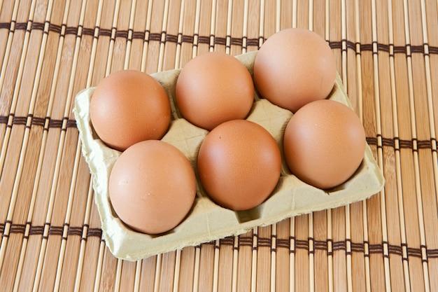 Foto van de helft dozijn eieren op bamboe tafellaken