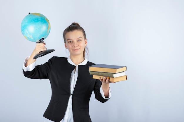 Foto van de jonge boeken en de bol van de leraarsholding op wit.