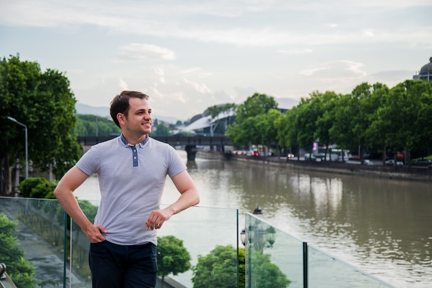 Foto van de jonge mens die dichtbij de rivier bij europese groene stad blijft. knappe jongen outdoor portret