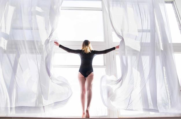 Foto van de jonge vrouw staat voor het raam tussen de open gordijnen