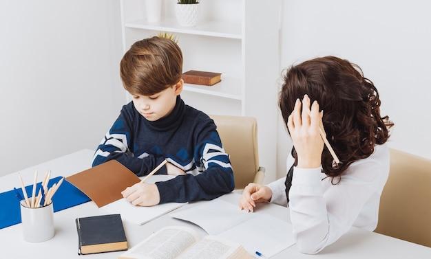 Foto van de jongen die zijn huiswerk doet en zijn moeder helpt hem.