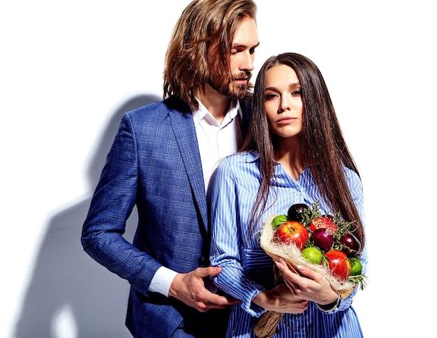 Foto van de knappe elegante man in pak met mooie vrouw in kleurrijke jurk met vers boeket