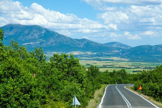 Foto van de mooie asfaltweg voor prachtige veld en berg achtergrond in griekenland