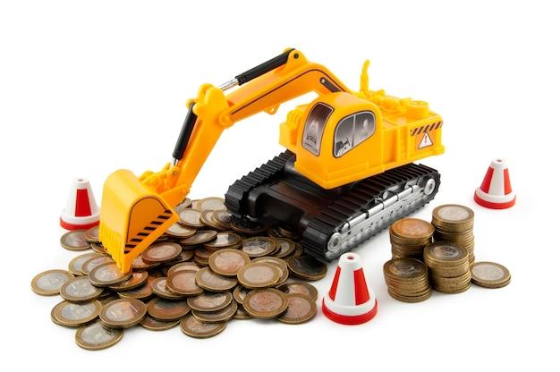 Foto van de speelgoedbulldozer en de hoop munten (geïsoleerd op wit)