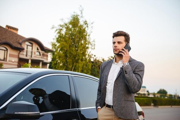 Foto van de succesvolle bedrijfsmens die kostuum draagt, zich dichtbij zijn luxe zwarte auto bevindt en op smartphone spreekt