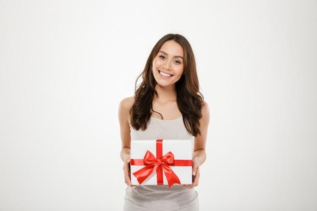 Foto van de tevreden doos van de vrouwenholding gift-verpakt met rode boog die opgewekt en verrast worden om verjaardagsgeschenk te krijgen, dat over wit wordt geïsoleerd