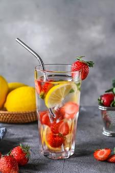 Foto van de verfrissende zomer bevroren koude drank. met aardbeien doordrenkt water. mineraalwater met verse aardbeiencitroen met een grijze achtergrond. detox water met aardbeicitroen. kopieer ruimte.
