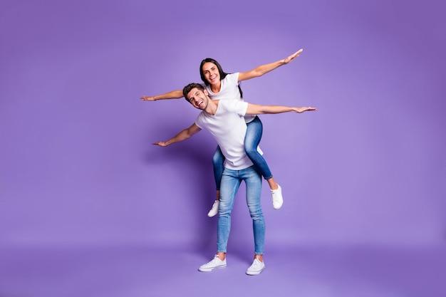 Foto van de volledige lengte van de lichaamsgrootte van vrolijk opgewonden positief stel met haar zijn rug te berijden met armen naar de zijkanten in wit schoeisel t-shirt jeans denim geïsoleerde pastel kleur violette achtergrond
