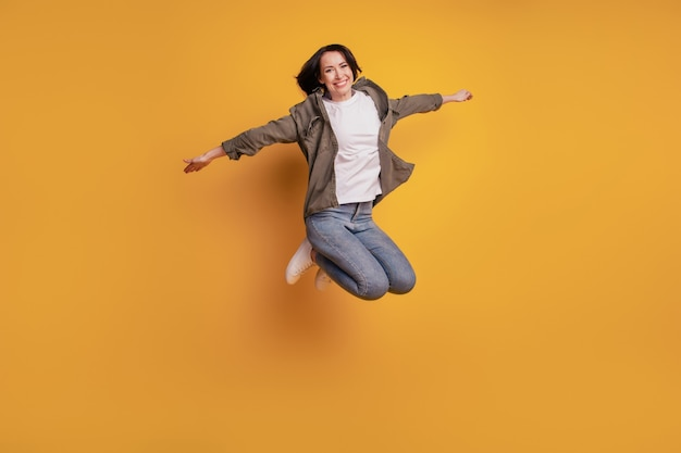 Foto van de volledige lengte van een jonge vrouw die vlieghanden opheft die geïsoleerd over gele achtergrond springen