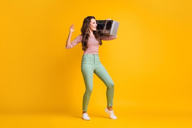 Foto van de volledige lengte van het lichaam van een jong meisje dat muziek luistert met retro boombox geïsoleerd op een levendige gele kleur achtergrond
