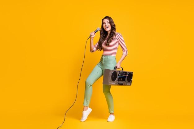 Foto van de volledige lengte van het lichaam van een vrouwelijke popster die een lied zingt dat retro boombox geïsoleerd houdt op een levendige gele kleur achtergrond