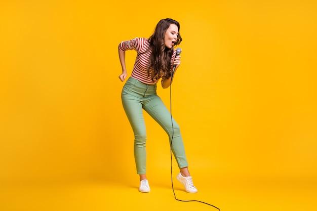 Foto van de volledige lengte van het lichaam van een vrouwelijke popster die een lied zingt op het podiumfestival geïsoleerd op een felgele achtergrond