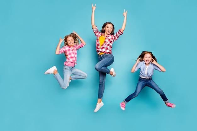 Foto van de volledige lengte van het lichaam van funky grappig opgewonden trendy familie die rockfans zijn die vreugdevol springen terwijl ze jeans denim wit dragen terwijl ze geïsoleerd zijn met blauwe achtergrond