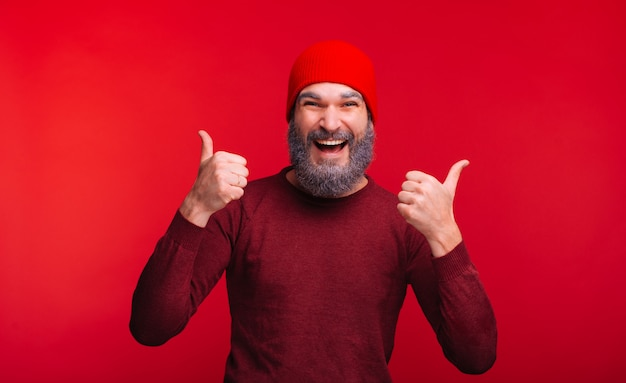 Foto van de vrolijke mens met witte baard die duimen over rode ruimte toont