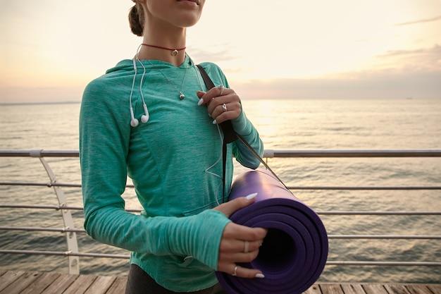 Foto van de vrouw die 's ochtends aan de kust yoga gaat beoefenen en een paarse yogamat vasthoudt.