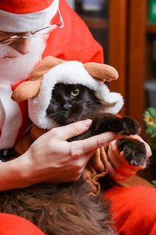 Foto van de zwarte kat van het nieuwe jaar in hertenkostuum in handen van de kerstman