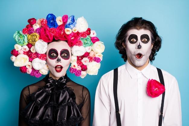 Foto van demon twee mensen man dame verbaasd open mond ondode vriend uitnodigen griezelig monster festival draag zwarte jurk dood kostuum rozen hoofdband bretels geïsoleerde blauwe kleur achtergrond