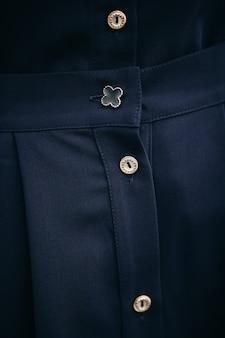 Foto van details van een mooie zwarte jurk gemaakt van dichte stof met nette pasvorm en witte knopen