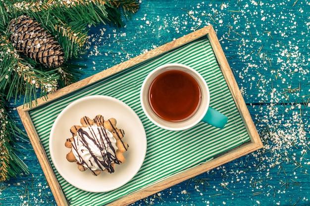 Foto van dienblad met mok thee en gebak op tafel met sparren, sneeuw en nieuwjaars versieringen