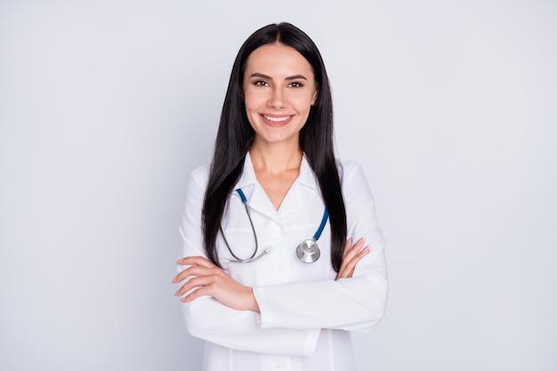 Foto van doktersvrouw die handen op grijze achtergrond kruisen