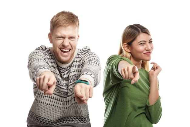Foto van dolblij extatisch jong kaukasisch paar bebaarde man en blonde vrouw naast elkaar staan, opgewonden blije blikken en wijzende vingers hebben, jou kiezen