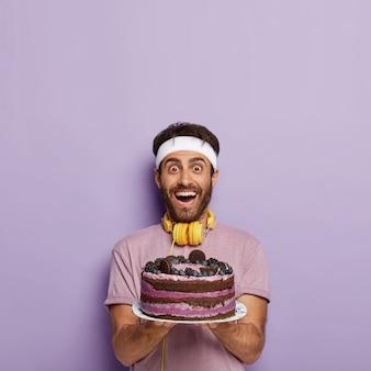 Foto van dolblij gelukkig sportman houdt grote gebakken fruitcake met bosbessen, wil iets zoets eten na een vermoeiende oefening in de sportschool, draagt vrijetijdskleding, koptelefoon voor het luisteren naar audio