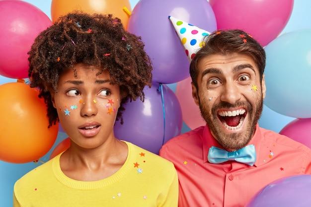 Foto van dolblij jong koppel poseren omringd door kleurrijke verjaardagsballons