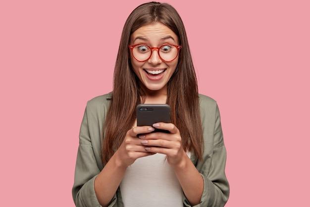 Foto van dolgelukkig meisje verliest toespraak van geluk, verbaasd over het ontvangen van goed nieuws in de boodschap