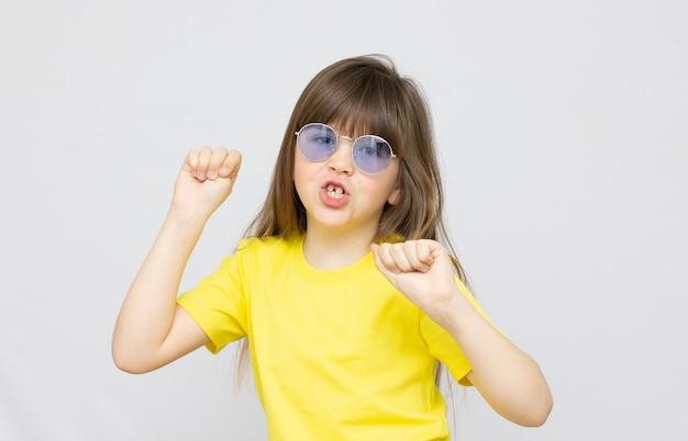 Foto van donkerbruin kapsel dat onder de indruk was van de dans van een klein meisje, een blauwe zonnebril en een gele t-shirtachtergrond