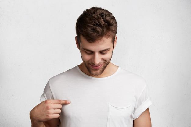 Foto van donkerbruin mannetje neerkijkt, wijst op lege t-shirt, zijnde in goed humeur