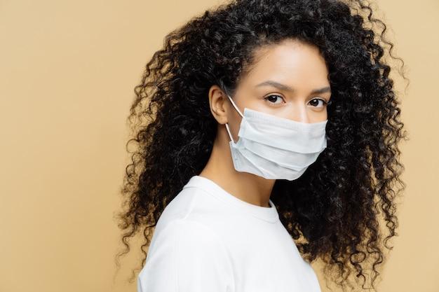 Foto van donkere huid afro-amerikaanse vrouw met krullend borstelig haar, draagt een beschermend masker tijdens de uitbraak van het coronavirus, geïsoleerd op beige achtergrond. ziekte voorkomen. virus, influenza, gezondheidszorg