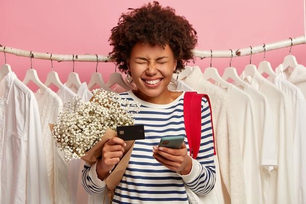 Foto van donkere huid meisje betaalt voor aankoop met creditcard en smartphone, poses op kledingwinkel met witte outfits op hangers, draagt boodschappentas, heeft dolgelukkig expressie