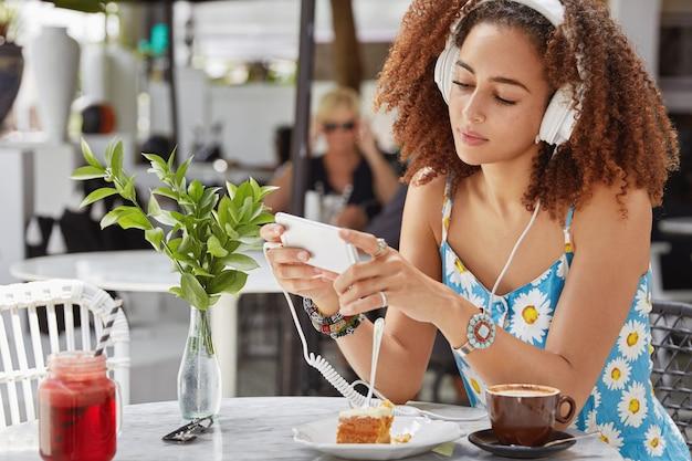 Foto van donkere vrouwelijke chats op mobiele telefoon, verbonden met draadloos internet in cafetaria, luistert favoriete liedje in afspeellijst met koptelefoon, geniet van koffie met cake