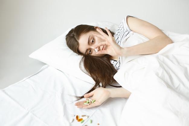 Foto van donkerharige student meisje dat een dag in bed doorbrengt, probeert te herstellen van de griep, houdt een heleboel kleurrijke pillen in handen en morst op een wit vel, kiest welke moet worden genezen