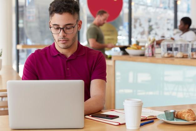 Foto van doordachte bebaarde man werkt aan creatieve ideeën voor publicatie, informatie over toetsenborden op draagbare laptopcomputer, brengt tijd door in coffeeshop, heeft heerlijke snack met croissant en thee