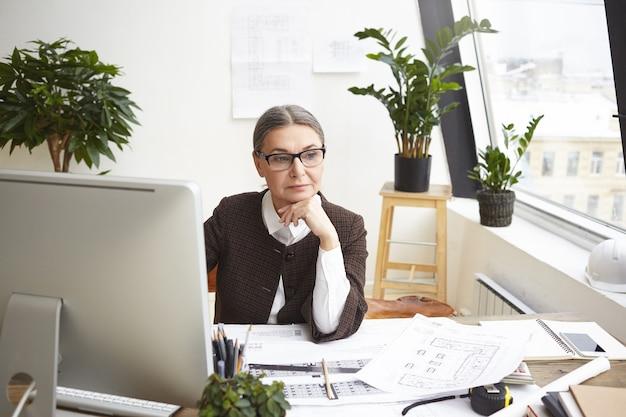 Foto van doordachte bekwame volwassen vrouwelijke constructeur-ingenieur in stijlvolle brillen met peinzende blik tijdens het ontwikkelen van bouwprojectdocumentatie, zit op bureau achter computer